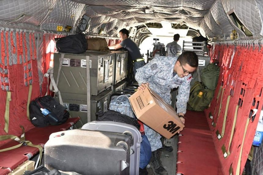 Republic of Singapore Air Force personnel loading supplies onto a Chinook bound for Royal Australian Air Force Base East Sale, Victoria.