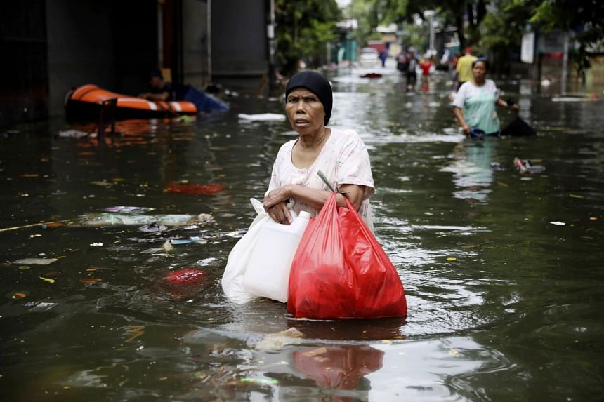 A woman wading through flood waters in Jakarta on Jan 4, 2020.