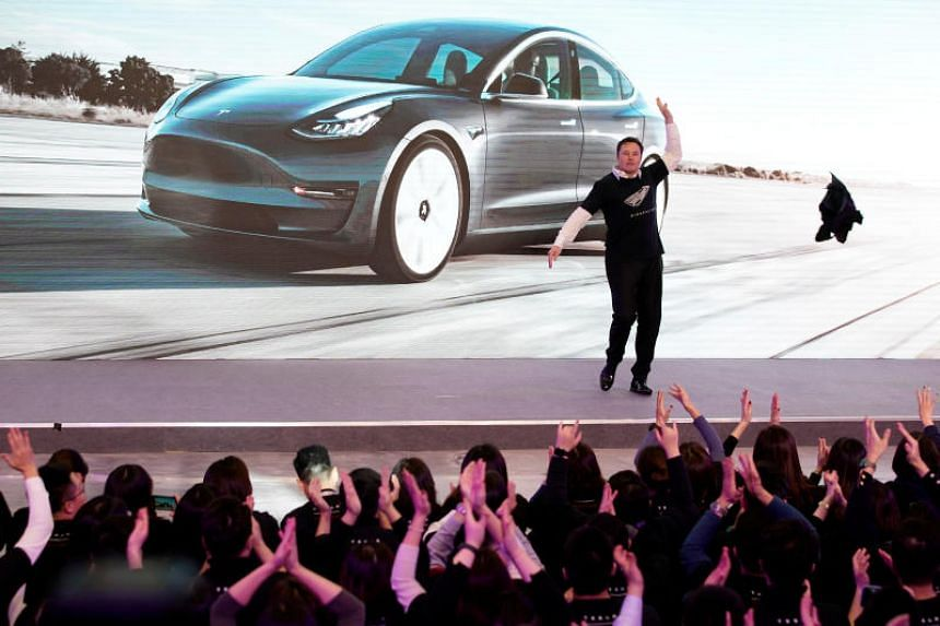 Tesla CEO Elon Musk takes off his coat onstage during a delivery event in Shanghai on Jan 7, 2020.