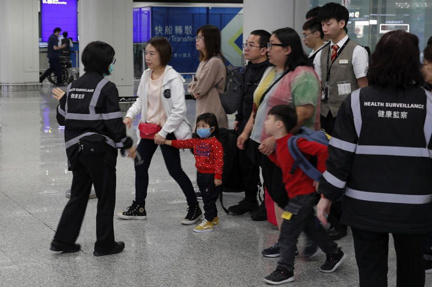 A photo taken on Jan 4, 2020, shows health surveillance officers guiding travellers at Hong Kong's international airport.