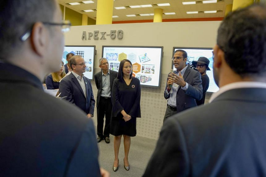 (From right) Nanyang Polytechnic's Deputy Director (Digital Engineering) Vinn Prabhu giving a tour at the launch of the NYP-StarHub Application & Experience Centre for 5G, alongside Nanyang Polytechnic Principal and CEO Jeanne Liew and StarHub chief