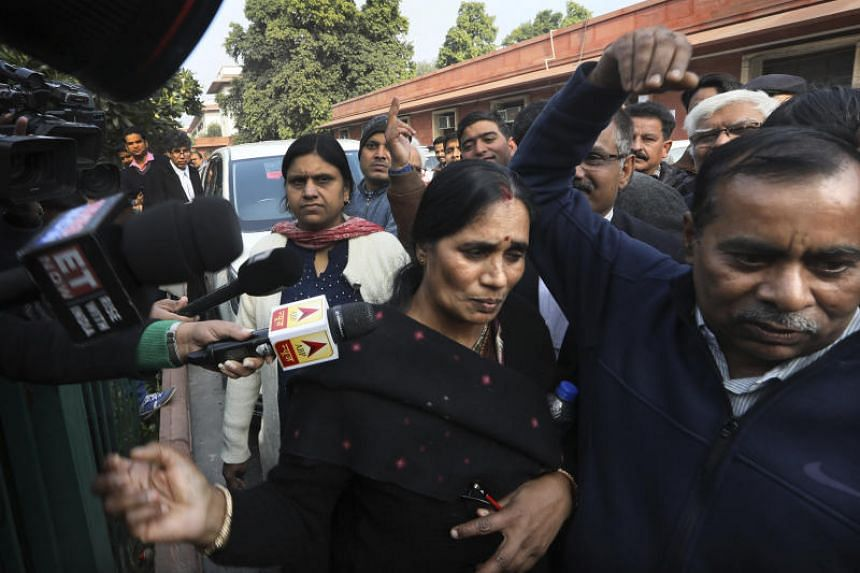Asha Devi (centre), mother of the victim of the fatal 2012 gang rape, walking with her husband Badrinath as they leave the Supreme Court in New Delhi on Dec 18, 2019.