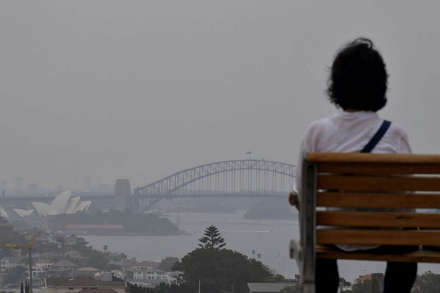 A woman sitting on a bench looks as smoke haze from bush fires blankets Sydney, Australia.