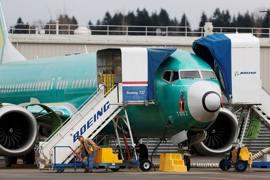 An employee works near a Boeing 737 Max aircraft at the company's facility in Renton, Washington.