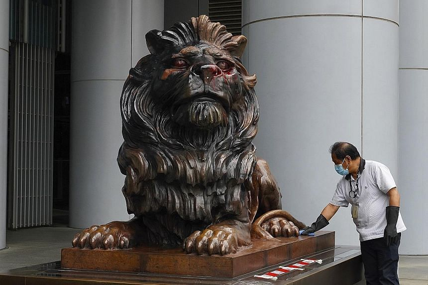A worker cleaning one of the two iconic HSBC bronze lion statues daubed with red and black paint by protesters in Hong Kong.