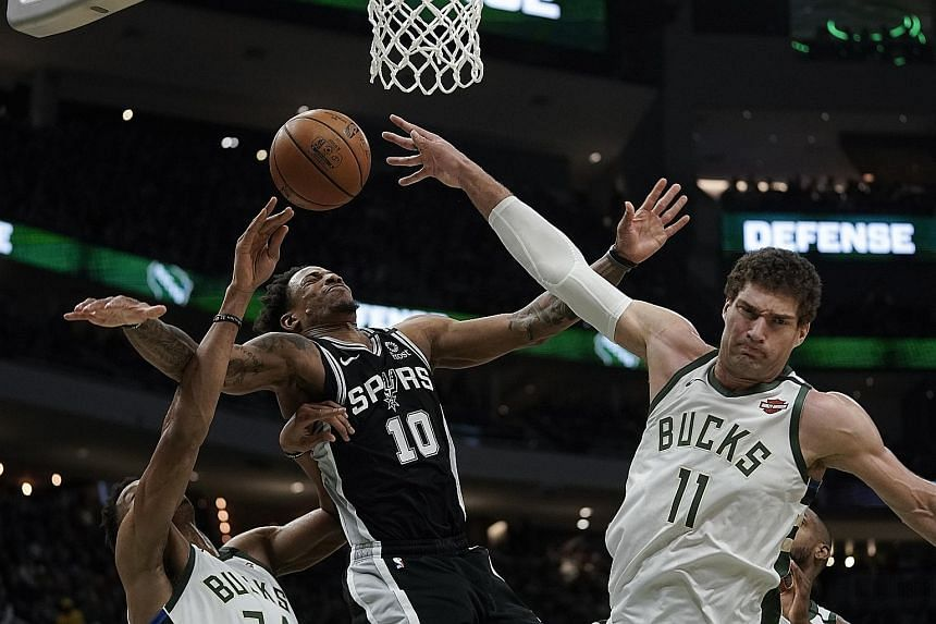 Milwaukee Bucks' Brook Lopez blocking a shot from DeMar DeRozan of the San Antonio Spurs during their NBA game on Monday. The Spurs won 126-104 to improve to 15-20, while the Bucks dropped to 32-6 but still have the best record in the league. PHOTO:
