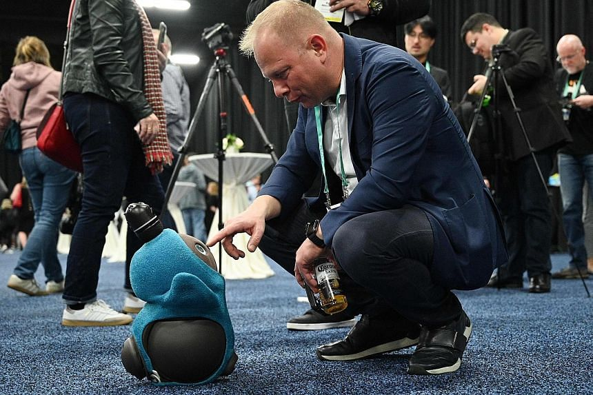 A visitor at the preview event of Consumer Electronic Show 2020 in Las Vegas on Sunday interacting with a Lovot companionship robot by Japanese firm Groove X. The robot is able to identify its owner through the use of artificial intelligence via faci
