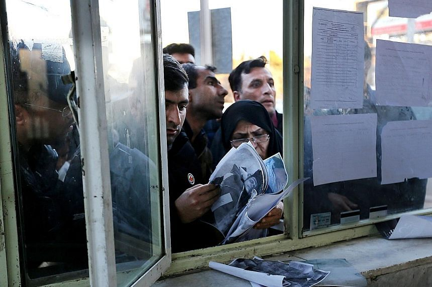 Relatives checking the lists of victims at the information office of a hospital in Kerman, Iran, following the stampede at the funeral of Iranian Major-General Qassem Soleimani yesterday. Above: People in New Delhi, India, protesting against US Presi