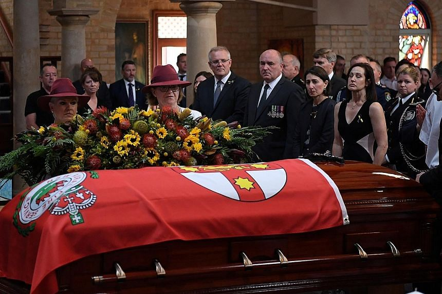 Australian Prime Minister Scott Morrison (centre), New South Wales (NSW) Emergency Services Minister David Elliott and NSW Premier Gladys Berejiklian (next to Mr Elliott) at the funeral service of NSW Rural Fire Service volunteer Andrew O'Dwyer in Sy