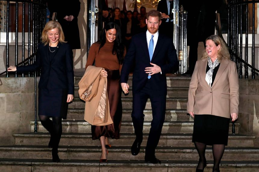 Harry and Meghan gesture as they leave after a visit to Canada House.