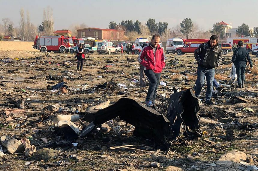 People walk near the wreckage after a Ukrainian plane carrying 176 people crashed near Imam Khomeini airport in Teheran early in the morning on Jan 8, 2020.