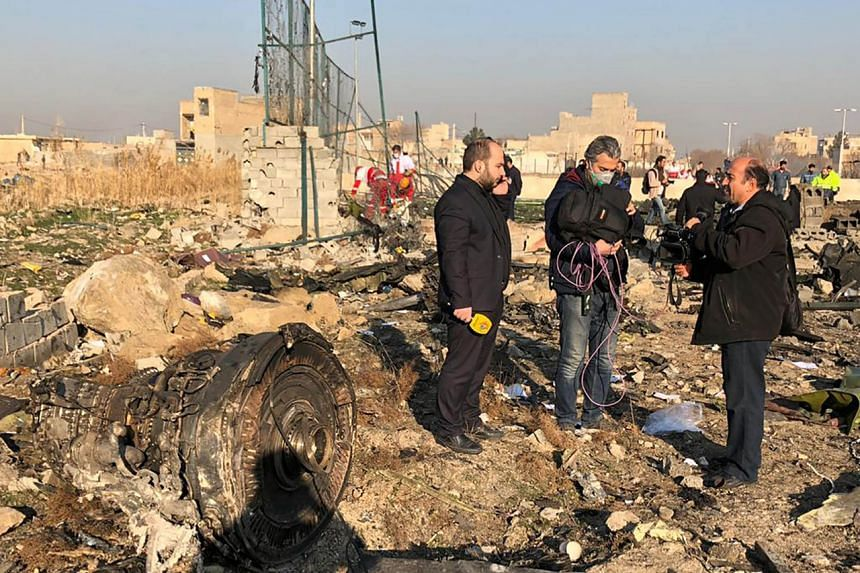 TV journalists stand amid the wreckage after a Ukrainian plane carrying 176 people crashed near Imam Khomeini airport in the Iranian capital Teheran early in the morning on Jan 8, 2020.