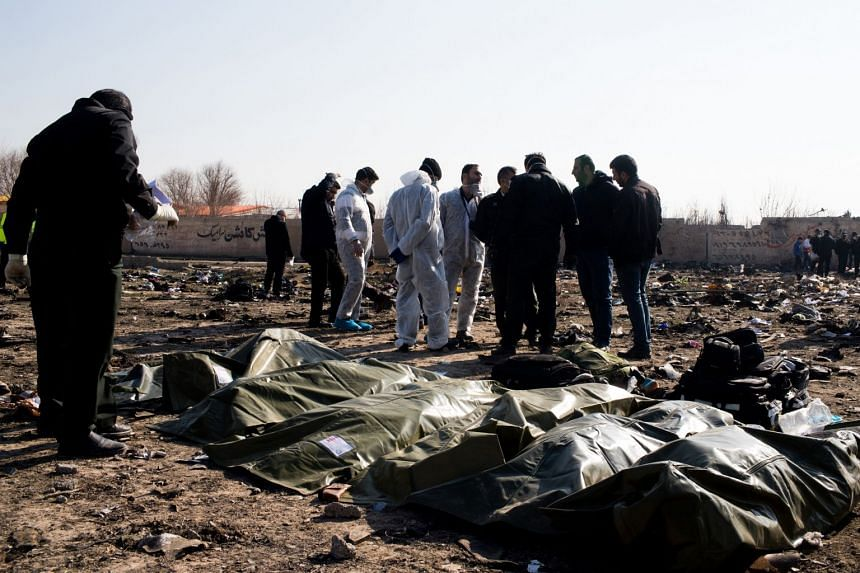 Bodies lie covered near the site of the crash on the outskirts of Teheran.