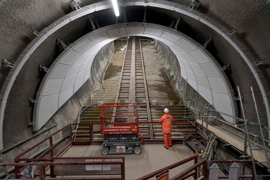An employee poses looking up an escalator that is under construction, on the platform level of the new Crossrail section of Farringdon Station in London on Feb 21, 2017.