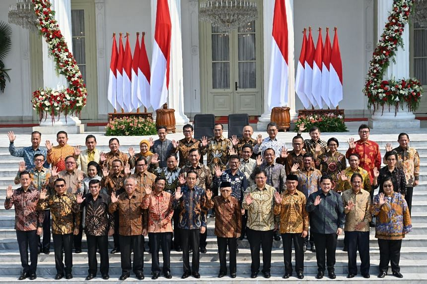 Indonesian President Joko Widodo and Vice President Ma'ruf Amin pose with members of their new cabinet on the steps of the Merdeka Palace in Jakarta, on Oct 23, 2019.