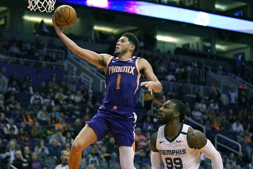 Phoenix Suns guard Devin Booker drives past Memphis Grizzlies forward Jae Crowder in the second half during an NBA basketball game, on Jan 5, 2020, in Phoenix.