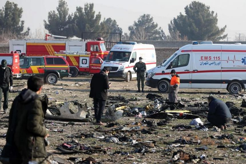 Rescue teams work amidst debris after a Ukrainian plane carrying 176 passengers crashed near Imam Khomeini airport in Teheran on Jan 8, 2020.