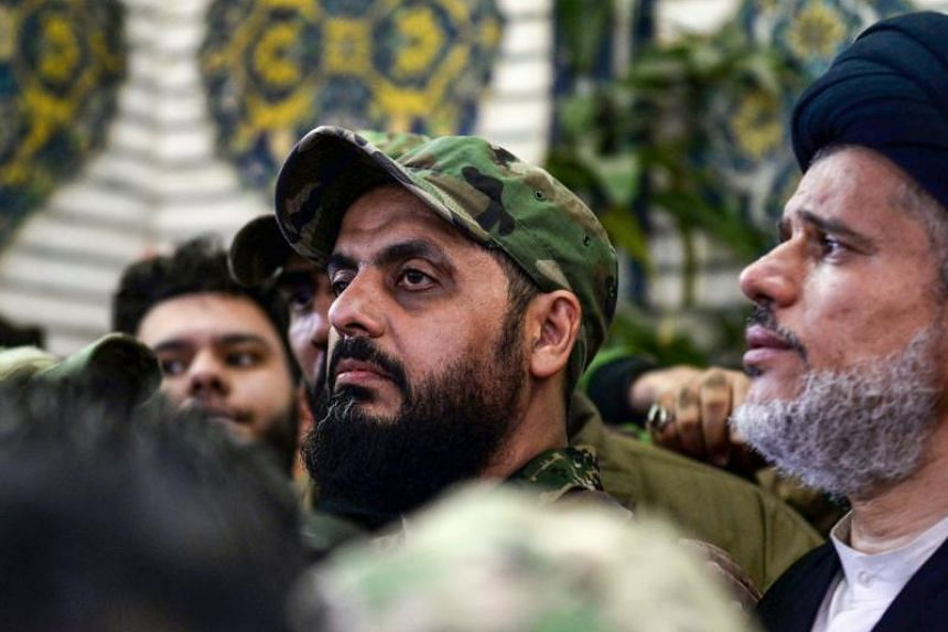 In a photo taken on Jan 4, 2020, Qais al-Khazali (centre), commander of the Asaib Ahl al-Haq pro-Iran faction, attends the funeral procession of slain Iraqi paramilitary chief Abu Mahdi al-Muhandis, Iranian military commander Qasem Soleimani and eigh