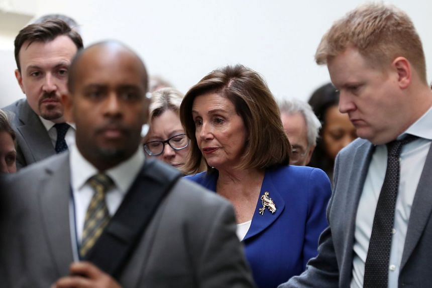 Nancy Pelosi answers questions from reporters after leaving a House Democratic caucus meeting on Capitol Hill in Washington.