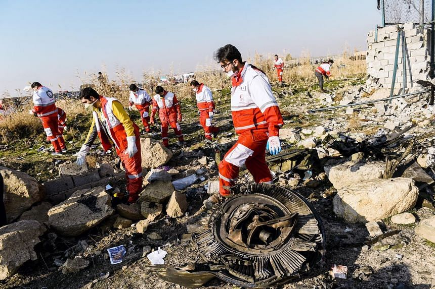 Rescue workers examining wreckage of the Boeing 737-800NG yesterday. The crash was Ukraine International Airlines' first fatal accident. Bodies of victims laid out at the site where the Ukraine International Airlines plane crashed after take-off from