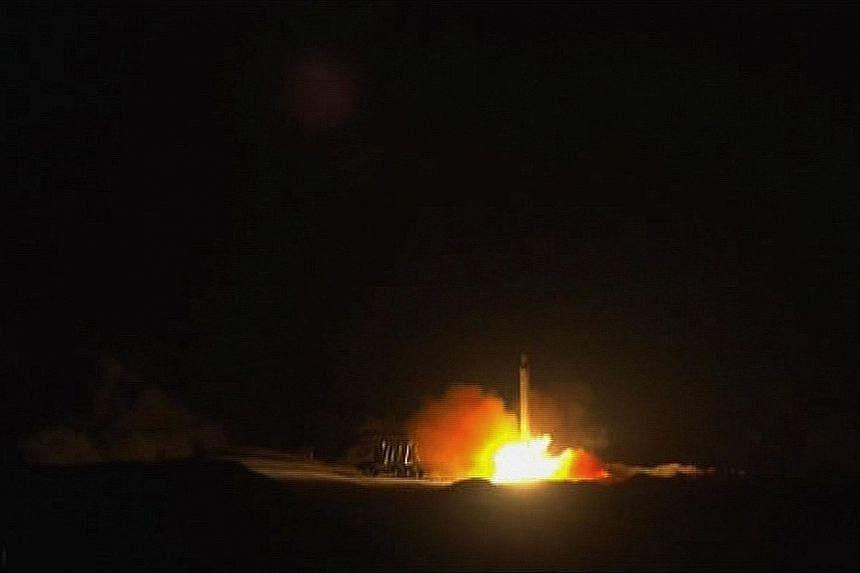 Above: Images from footage obtained from state-run Iran Press news agency which show missiles being fired into the night sky from Iran yesterday. PHOTOS: AGENCE FRANCE-PRESSE Right: Residents looking at a crater in the outskirts of Duhok, Iraq, cause