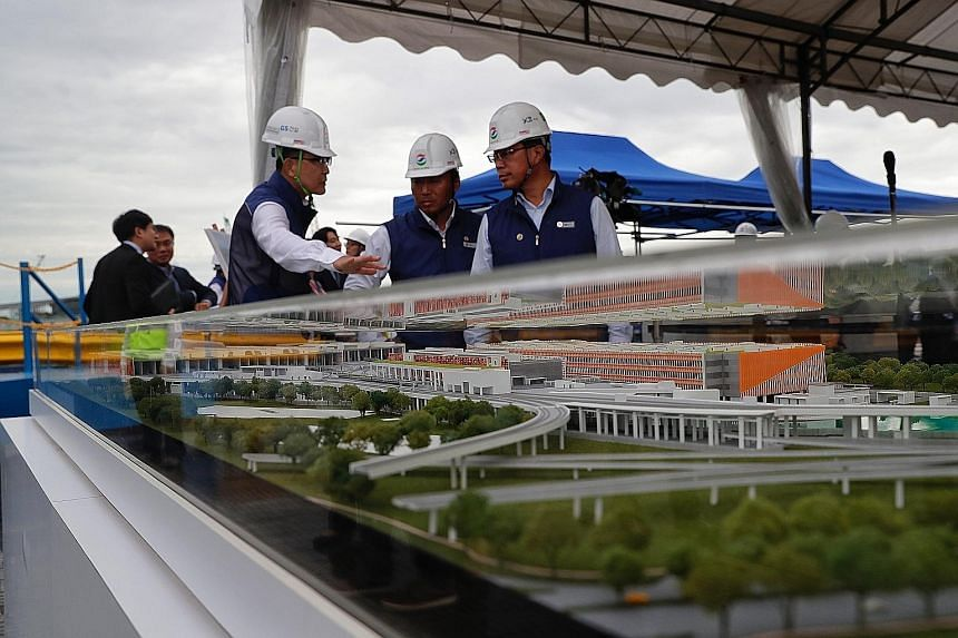 A 2018 photo of workers with a model of the Thomson-East Coast Line Integrated Depot. As construction demand is expected to remain robust, the Government is working with the industry to build better career and wage prospects.
