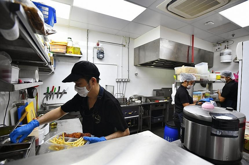 Right: Mr Ling Mee Kong, 42, head chef of Bowl & Grill, preparing an order in one of the GrabKitchen units yesterday. GrabFood's first multi-restaurant-brand space in Singapore brings its network of cloud kitchens to 50 across five countries in the S