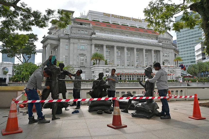 Workers cleaning and polishing the sculpture titled A Great Emporium in front of the Asian Civilisations Museum yesterday. The 3.6m by 3m bronze sculpture, along with three others making up The People Of The River sculptures along the Singapore River