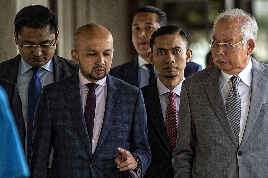 """Former Malaysian premier Najib Razak (right) at the Kuala Lumpur courthouse yesterday. He said he was """"shocked"""" over the airing of the clips and had referred the matter to his lawyer. His wife Rosmah Mansor did not deny or confirm whether the recordi"""