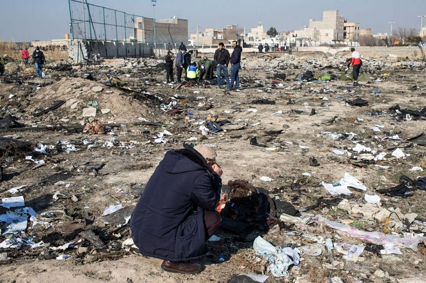 A relative of a passenger grieves at the site of the crash on the outskirts of Teheran.