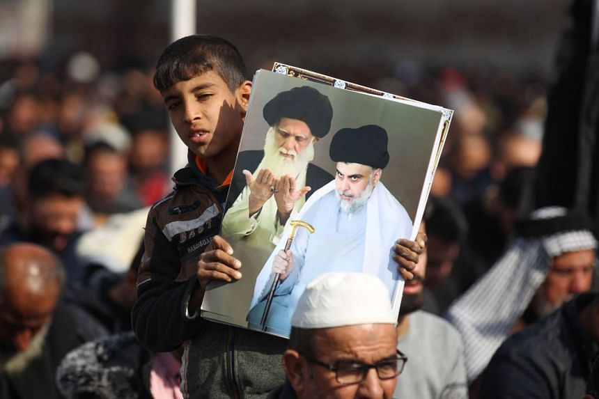 A young boy holds a poster showing top Shi'ite cleric Grand Ayatollah Ali Sistan (left) and Shi'ite cleric Moqtada al-Sadr during Friday prayers in Baghdad's Sadr City suburb.