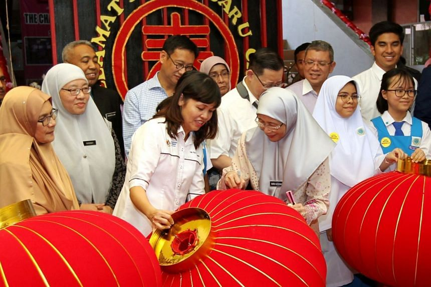 Deputy Prime Minister Wan Azizah and Deputy Education Minister Teo Nie Ching (both centre) visiting the school which was asked to remove the CNY decorations.
