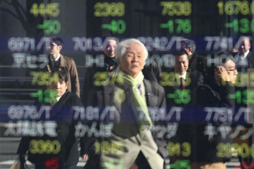 People are reflected as they cross a street in front of a stock indicator showing share prices of Japanese companies in Tokyo, on Jan 6, 2020.
