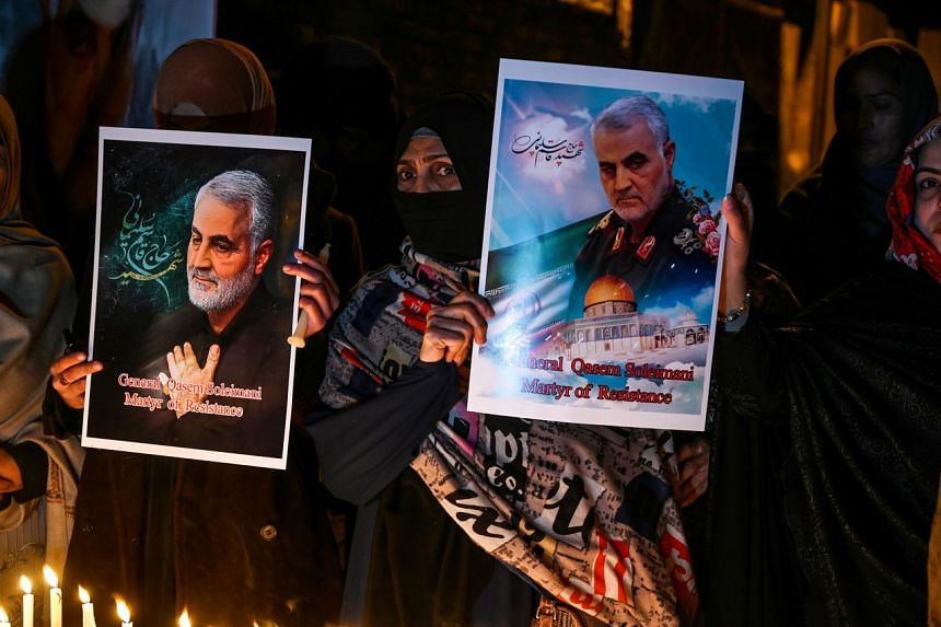 Shi'ite Muslims hold pictures of slain top Iranian general Qassem Soleimani to pay him tribute during a candlelight vigil in Islamabad on Jan 8, 2020.