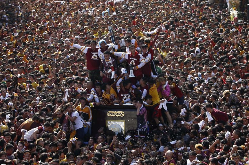 Catholic devotees surround the Black Nazarene statue as it is taken on procession to mark its feast day in Manila, Philippines, on Jan 9, 2020.