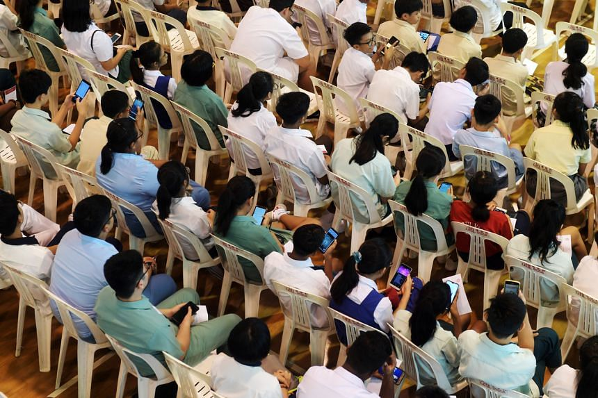 Students using their phones during an event in Ang Mo Kio, on Jan 4, 2020.