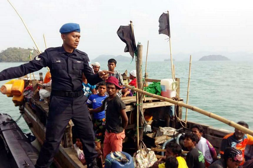 A photo taken on April 3, 2018, shows a Malaysian Maritime Enforcement Agency officer on a boat carrying Rohingya refugees, after it was intercepted off Langkawi.