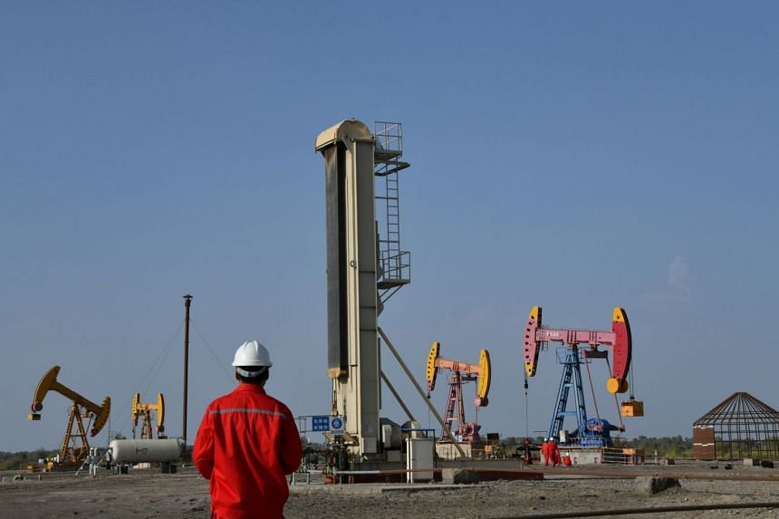 Workers are seen near pumpjacks at an oil field in China on Aug 7, 2019.