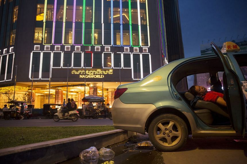 In a file photo taken on Oct 24, 2017, a taxi driver sleeps near the NagaWorld casino complex in Phnom Penh.