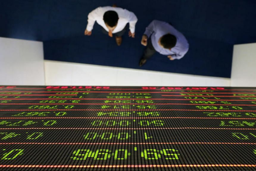 Investors walk under a stock index board at the Dubai Financial Market in the United Arab Emirates.