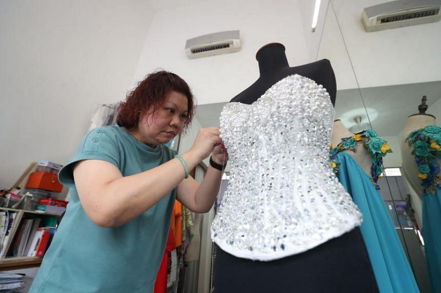 Tailor Suzanne Chua,  co-founder of Zann & Denn's, hand-beading a corset.