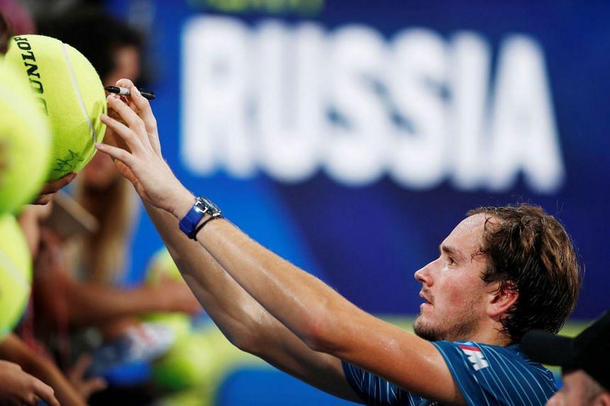 Russia's Daniil Medvedev signs autographs after winning against Argentina's Diego Schwartzman.