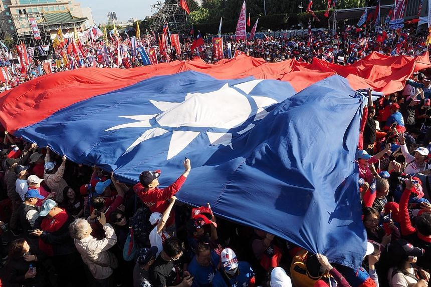 Supporters of Taiwan's Kuomintang (KMT) presidential candidate Han Kuo-yu carrying a giant KMT flag at a campaign event in Taipei yesterday.