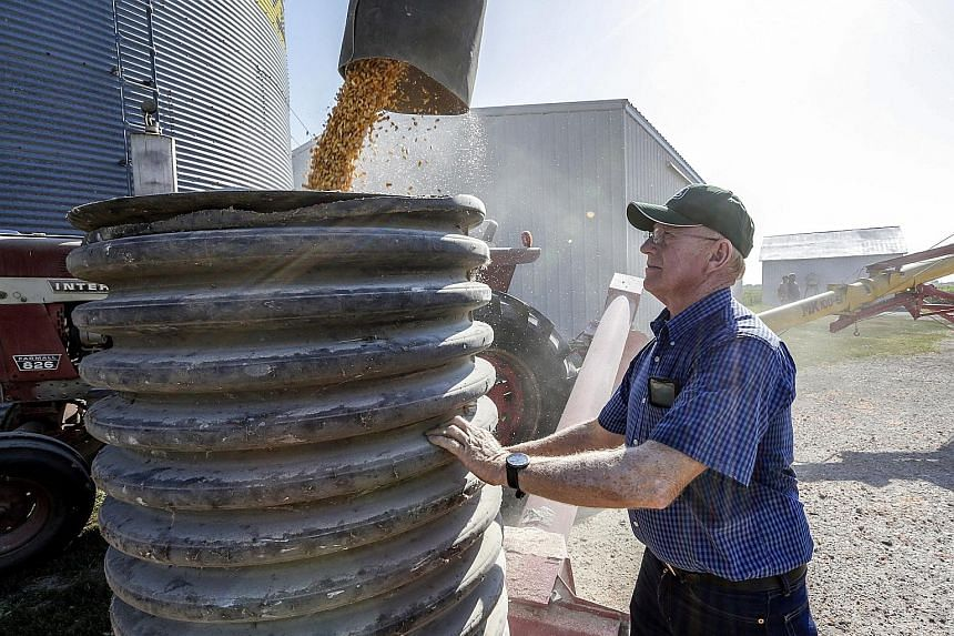 US farmer Don Bloss checking on the operation of an auger transferring corn on his farm in Pawnee City, Nebraska, in this 2018 file photo. Trade tensions between the United States and China cooled with the announcement of a so-called phase one trade