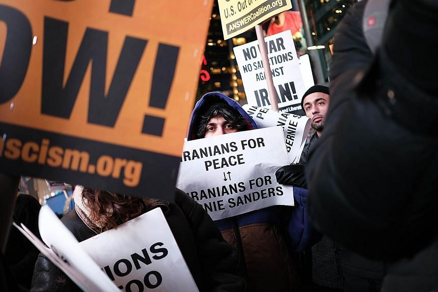 """Demonstrators at a protest in Times Square against military conflict with Iran in New York City on Wednesday. President Donald Trump has vowed to impose more sanctions against Iran but also said """"the United States is ready to embrace peace with all w"""
