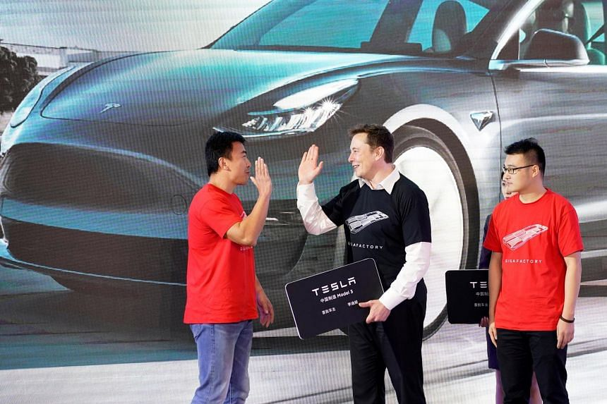 Tesla chief executive Elon Musk on stage with owners of the China-made Tesla Model 3, at a delivery event held in its Shanghai factory on Tuesday. PHOTO: REUTERS