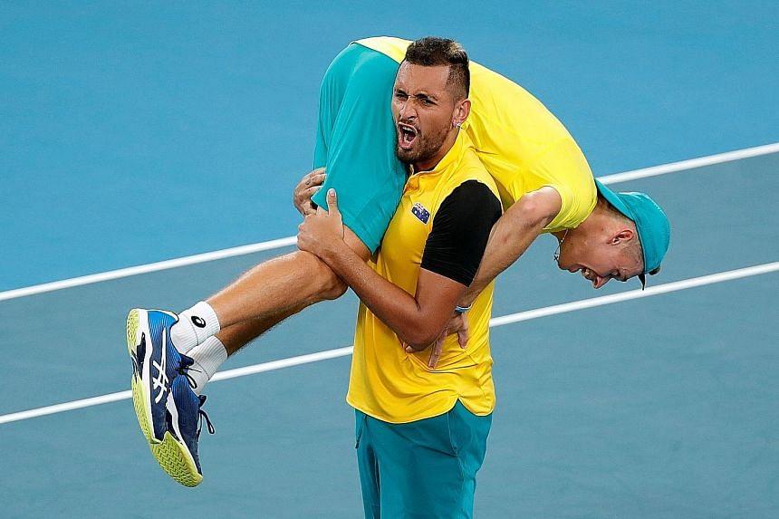 Australia's Nick Kyrgios carrying Alex de Minaur off the court following their 2-1 quarter-final win over Britain yesterday. They will play Belgium or Spain in the semi-finals on Saturday. PHOTO: REUTERS