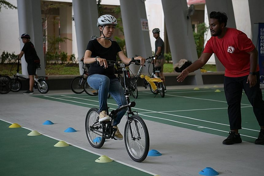 A former e-scooter rider participating in a safe riding programme organised by NTUC in an open area near GrabFood's e-Scooter Trade-In Grant Centre yesterday.