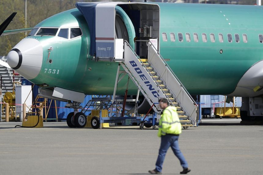 A worker walks past a Boeing 737 Max 8 airplane in US on April 26, 2019.