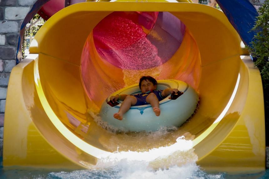 In a photo taken on Jan 3, 2020, a young boy enjoys a water slide ride on a clear day at a park in Bangkok.